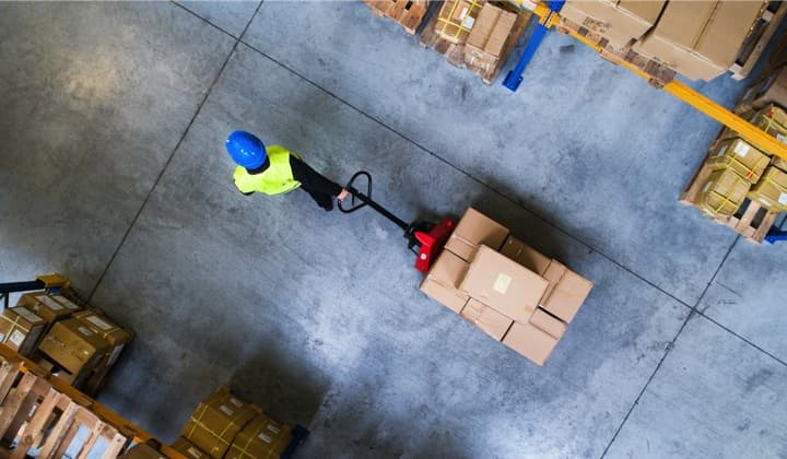 A birdeye view of a warehouse floor with a worker pulling a stack of boxes on a cart.