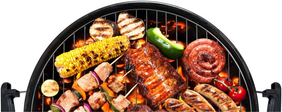 A birdseye photo of a charcoal grill with an assortment of barbecued meats and vegetables.