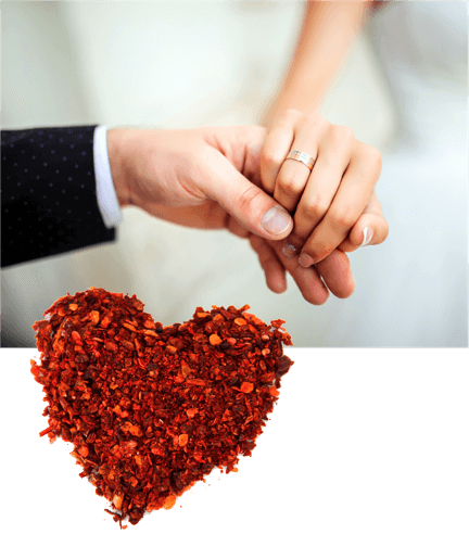 A photo shoing a bride and groom holding hands, overlayed with a stylized Valentine heart made from an assortment of ground spices.