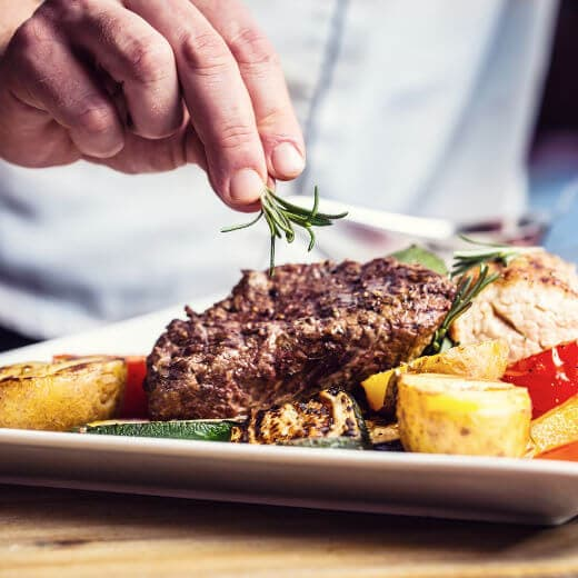 A photo of a chef's hand adding finishing touches to a dish of steak with grilled vegetables.